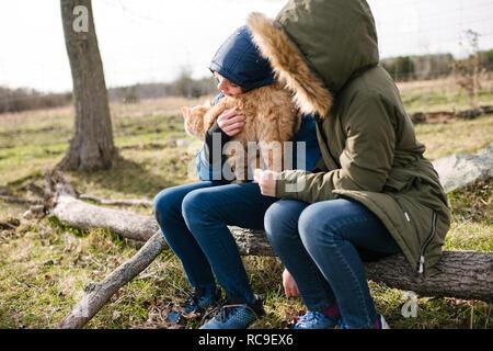 Bruder und Schwester kuscheln Katze im Feld - Stockfoto
