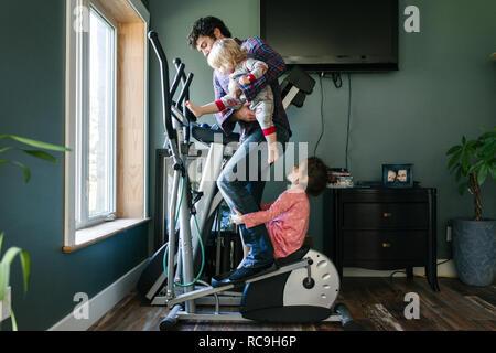 Vater und Kinder spielen auf elliptischen Maschine - Stockfoto
