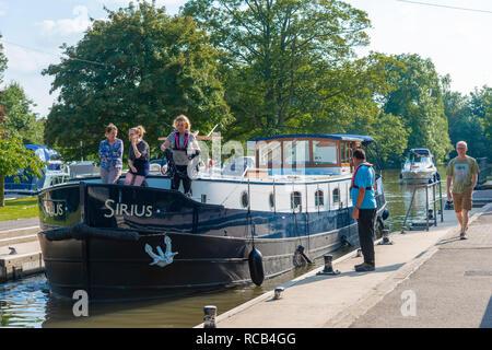 Schleusenwärter beobachten Barge und Cruiser eingabe Hurley Sperren im Sommer auf der Themse in Hurley in der Nähe von Maidenhead, Berkshire, Großbritannien - Stockfoto