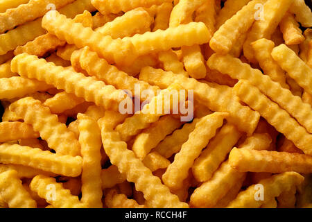 Nahaufnahme Hintergrund der Crinkle cut knusprige Golden fried Potato Chips, Pommes frites, Pommes Frites Inn a full frame anzeigen - Stockfoto