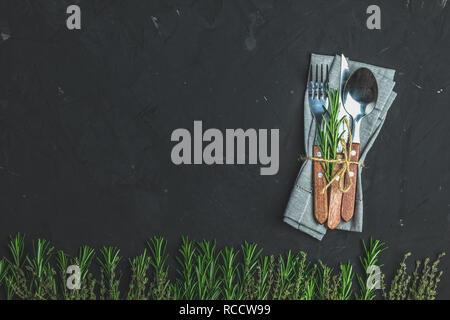 Rustikale vintage Set Besteck Messer, Löffel, Gabel. Schwarzer Stein Betonoberfläche Hintergrund. Ansicht von oben, kopieren. - Stockfoto