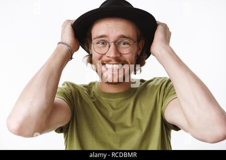 Taille- schuss besorgt und ängstlich Ausgeflippt überwältigt junger bärtiger Mann mit durchbohrten Nase, Hände auf Hut Aufeinanderpressen der Zähne und die Stirn in Panik, ständigen nervösen über grauer Hintergrund - Stockfoto