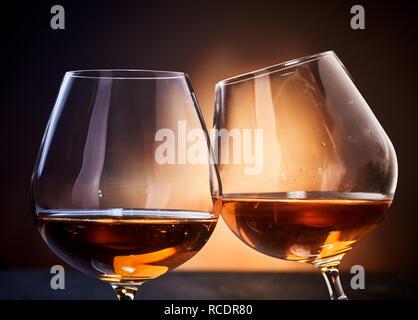 Zwei Gläser cognac Klirren in close-up gegen dunkelbraunen Hintergrund - Stockfoto