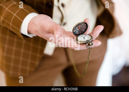 Ein Mann in einem braun-karierten Anzug hält in seiner Hand ein geöffnetes Taschenuhr, die sichtbar ist. Schließen Foto - Stockfoto