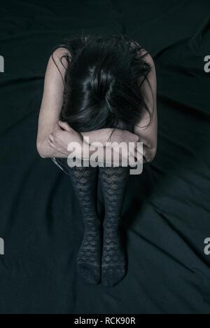 Miserable junge Frau Kopf auf Knie - Stockfoto