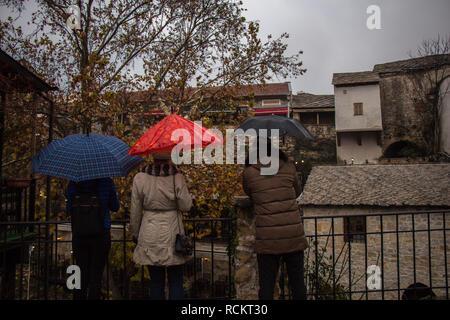 Drei Personen mit Sonnenschirmen. Straße in der Altstadt von Mostar. - Stockfoto
