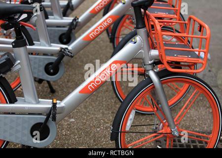LONDON, ENGLAND - Januar 15, 2019: Mobike dockless Fahrräder in einer Straße geparkt. Mobike ist ein Bike Sharing Plattform für die kurzen Strecken. - Stockfoto