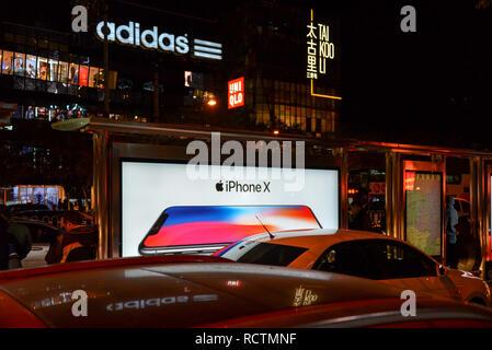 Peking, China - November 11, 2017: Night Shot in Sanlitun, einer geschäftigen Einkaufsstraße, mit Reklametafeln ad für die Freigabe, wenn das iPhone X. Adidas und Uniq - Stockfoto