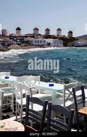 """Stühle und Tische von einem Pub, alte Häuser am Meer, """"Klein Venedig"""" Viertel, Altstadt von Mykonos Stadt, Mykonos, Griechenland, Europa - Stockfoto"""