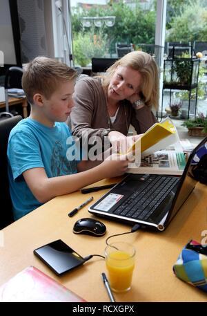 Junge, der seine Hausaufgaben zu Hause, und seine Mutter hilft ihm - Stockfoto