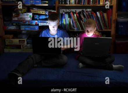 Geschwister, ein Junge, 12 Jahre alt, und ein Mädchen, 10 Jahre alt, Spielen von Computerspielen auf Laptop Computer in Ihrem Zimmer - Stockfoto