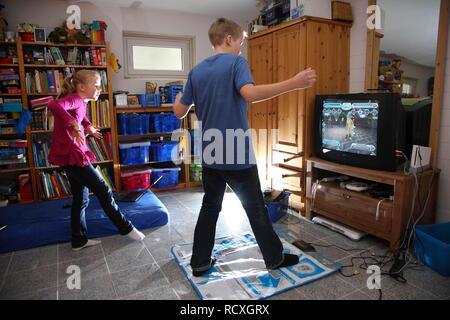 Geschwister, ein Junge, 12 Jahre alt, und ein Mädchen, 10 Jahre alt, spielen, Tanz Spiel auf Wii Spiele in Ihrem Zimmer Konsole zusammen - Stockfoto