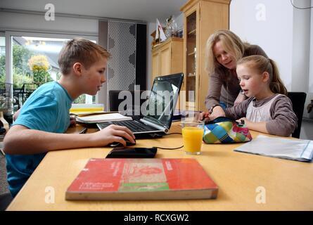 Geschwister ihre Hausaufgaben im Wohnzimmer, ihre Mutter ist Ihnen zu helfen - Stockfoto