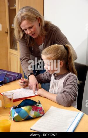 Mädchen machen ihre Hausaufgaben zu Hause, ihre Mutter ist Ihr hilft - Stockfoto