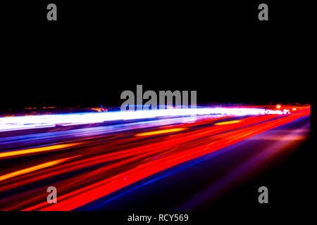 Autos leichte Wanderwege auf einer gekrümmten Autobahn bei Nacht. Traffic Night Trails. Bewegungsunschärfe. Nacht Stadt Straße mit verkehr Scheinwerfer Bewegung. Stadtbild. Leuchten - Stockfoto