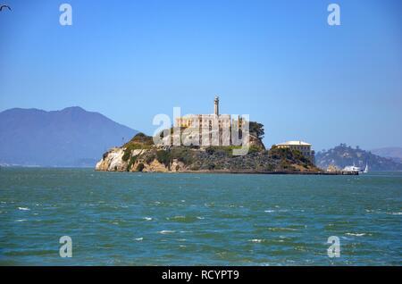 Die Insel Alcatraz in der Bucht von San Francisco, Fähre an der Anlegestelle, Hügel im Hintergrund, welliges Meer, blauer Himmel, sonnig, Blick vom Pier 39, Sommer - Stockfoto