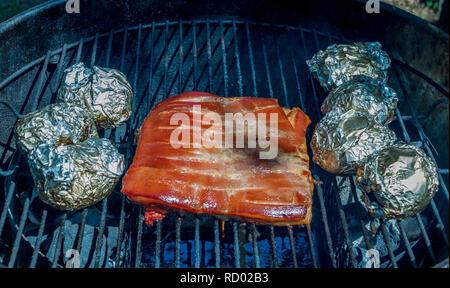 Rotes Fleisch und Kartoffeln in Alufolie langsam kochen in einem outdoor Wasserkocher Backofen Bild im Querformat verpackt - Stockfoto