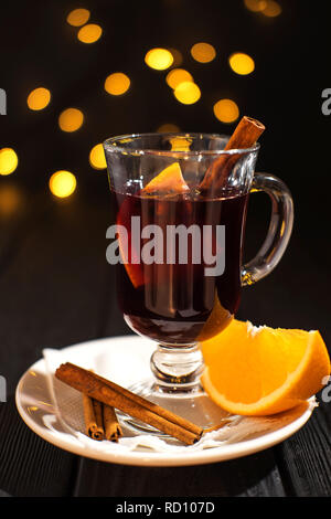 Glühwein mit Zutaten auf den Tisch und Weihnachtslichter auf Hintergrund, Zimt in der Glas-, Stück orange - Stockfoto