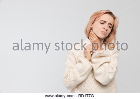 Studio Portrait von jungen ungesunde blonde Frau in warmen Pullover Holding ihre Kehle/leidet unter Kälte und Grippe, starken Halsschmerzen, Übelkeit. - Stockfoto
