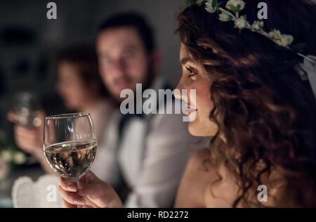 Eine Nahaufnahme einer jungen Braut an einem Tisch auf einer Hochzeit sitzend, mit einem Glas Wein. - Stockfoto