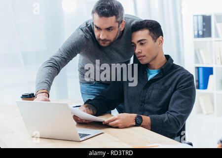 Zwei konzentrierte sich Geschäftsleute arbeiten mit Papieren und Laptop im Büro - Stockfoto
