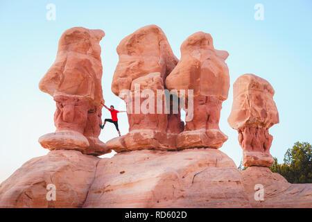 Schöne Sicht der männlichen Wanderer stehen zwischen erstaunliche Vier Hoodoos Sandstein Felsformationen in Devil's Garten im schönen Abendlicht bei Sonnenuntergang - Stockfoto