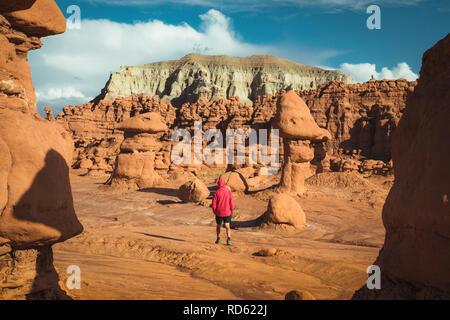 Panoramablick auf Wanderer in Red Jacket wandern im Goblin Valley State Park inmitten wunderschöner hoodoos Sandsteinformationen, Utah, USA - Stockfoto