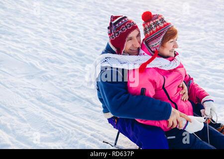 Senior paar Schlitten bergab. Familie Spaß haben, sitzen auf dem Schlitten im Winter Park. Valentinstag Konzept - Stockfoto