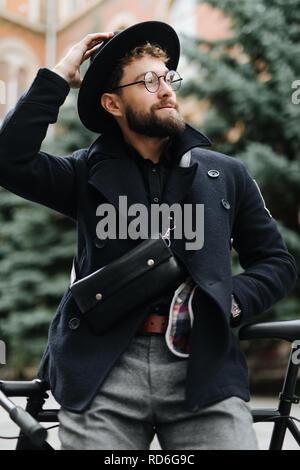 Portrait von gut aussehenden bärtigen Mann in legere Kleidung weg schauen und lächeln und lehnte sich auf seinem Fahrrad stehen im Freien