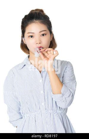 Schöne chinesische amerikanische Frau trägt ein Kleid und das Rauchen einer Zigarette auf weißem Hintergrund - Stockfoto