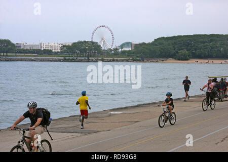 Menschen joggen und Fahrrad fahren auf Navy Pier in Chicago, IL, USA - Stockfoto