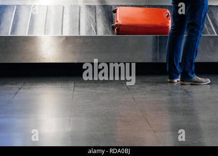 Ansicht der Rückseite ein Geschäftsmann auf ihr Gepäck am Förderband mit schönen roten Koffer auf dem Band - Stockfoto