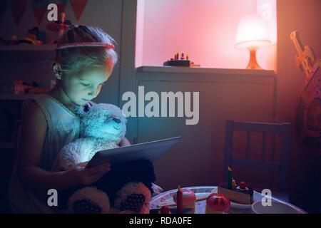 Kleines Kind mit Bär und Tablet sitzen bei Tisch und in der Nacht. Horizontale drinnen geschossen. - Stockfoto