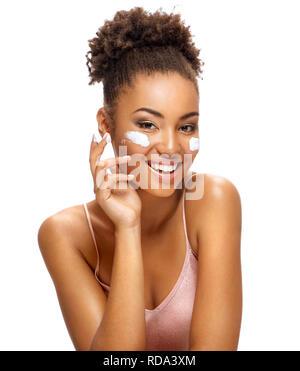 Аttractive Mädchen Anwendung Feuchtigkeitscreme. Fotos von lächelnden afrikanische amerikanische Mädchen mit gesunder Haut auf weißem Hintergrund. Hautpflege und Schönheit anhand von quantitativen Simulatio - Stockfoto