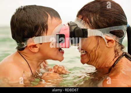 Grinsend Mitte der erwachsenen Frau und ihr Sohn Gesicht im Ozean zu Gesicht beim Tragen von Scuba Masken. - Stockfoto