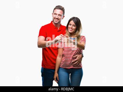 Junge Paare, die in Liebe über isolierte Hintergrund lächelnd in Liebe mit Herz und Formen mit den Händen. Romantische Konzept. - Stockfoto