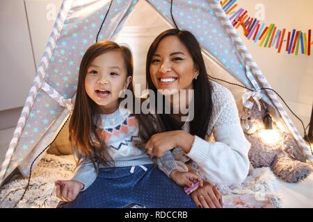Foto eines glücklichen jungen asiatischen Frau mit ihrer kleinen Tochter Spaß auf dem Boden. Weihnachten Konzept. - Stockfoto