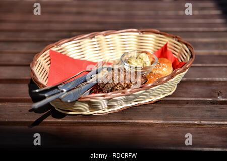 Korb mit Brot und Besteck auf braune Holztisch. Selektive konzentrieren. - Stockfoto