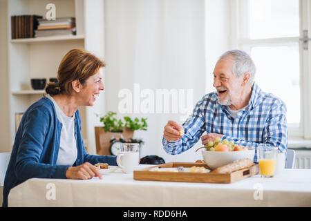 Ein älteres Paar am Tisch zu Hause sitzen, frühstücken. - Stockfoto