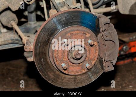 Ein Auto mit dem vorderen Rad entfernt, wo Sie die Bremsscheibe sehen können. - Stockfoto