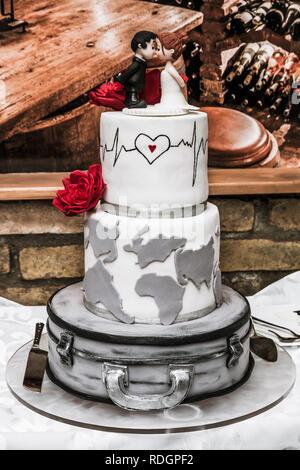 Weisse Hochzeitstorte mit roten Rosen, Heartbeat Rate und Figuren auf dem Tisch im Restaurant. - Stockfoto