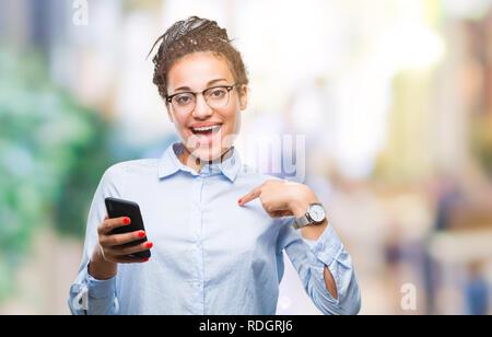 Junge geflochtenes Haar african american business Mädchen mit Smartphone über isolierte Hintergrund mit Überraschung Gesicht zeigenden Finger zu sich selbst - Stockfoto