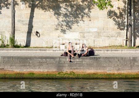 Junge Leute sitzen entlang der Ufer des Canal St-Martin in Paris, Frankreich. - Stockfoto