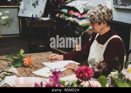 Ältere Frau Brille, rotes Kleid und der weißen Schürze am Tisch sitzen, arbeiten auf Bleistiftzeichnung von Orange Dahlie. - Stockfoto