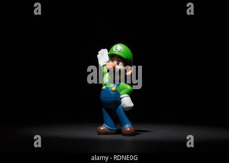 Moskau, Russland - Januar 18, 2019: Kunststoff Abbildung von Luigi, eine fiktive Figur von Nintendo Videospiele stehen auf dunklen Untergrund und beleuchtet von oben. - Stockfoto