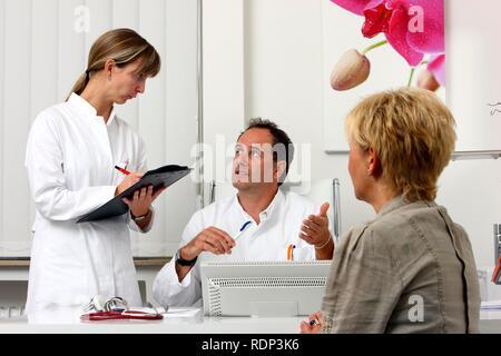 Die medizinische Praxis, Arzt im Gespräch mit einem Patienten und ein medizinischer Techniker, um über eine Prüfung - Stockfoto