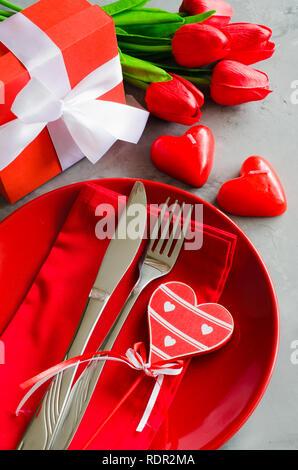 Festliche Tischdekoration für den Valentinstag mit Geschenkbox, Tulpen und Kerzen in der Form von Herzen. - Stockfoto