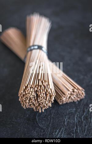 Soba Nudeln - traditionelle asiatische Lebensmittel Zutat. Bündel von Buchweizen Soba Nudeln auf den schwarzen Stein, Ansicht von oben, kopieren. - Stockfoto