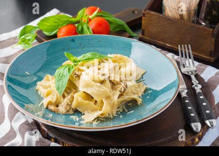 Italienische Nudeln Pappardelle mit gemischten Pilzen, cremige Käse Sauce und Parmesan. Mit Basilikum serviert. - Stockfoto