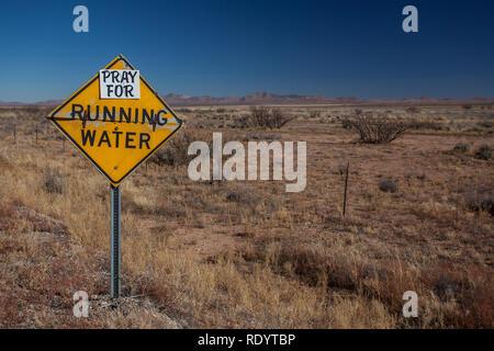 Beten Sie für fließendes Wasser eine humorvolle Zeichen zu Dürre im Südwesten von New Mexico, im Zeitalter des globalen Klimawandels - Stockfoto